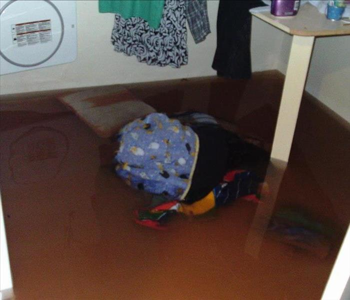 Laundry room floor flooded due to broken washing machine.