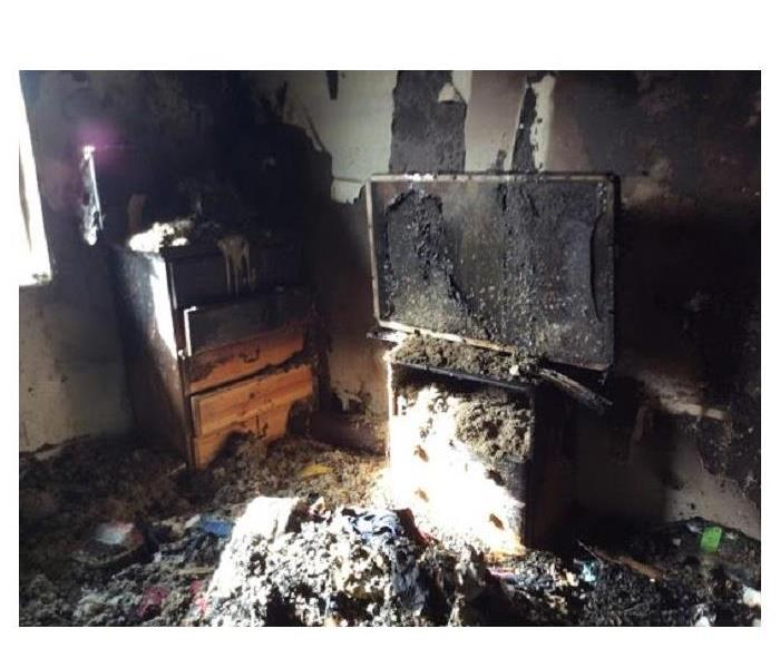 Living room, TV and other belongings damaged with smoke and soot.